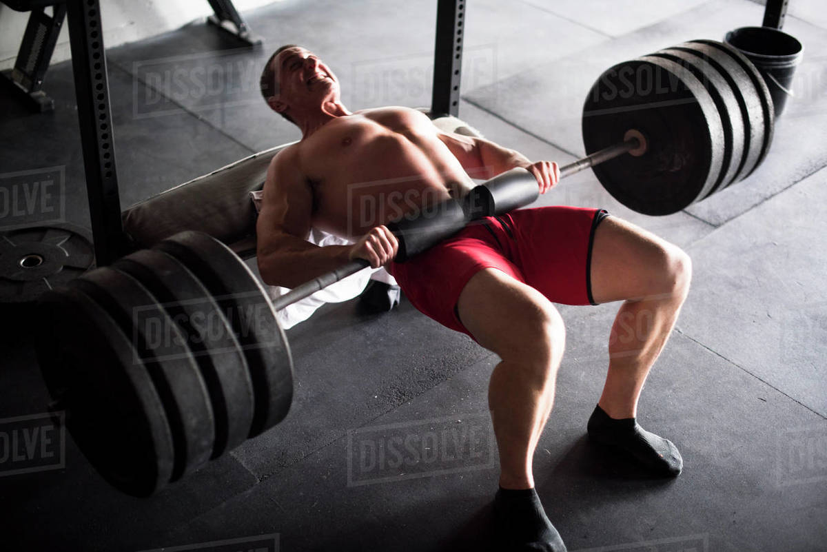 An athlete doing weighted hip thrusts at a gym. Royalty-free stock photo