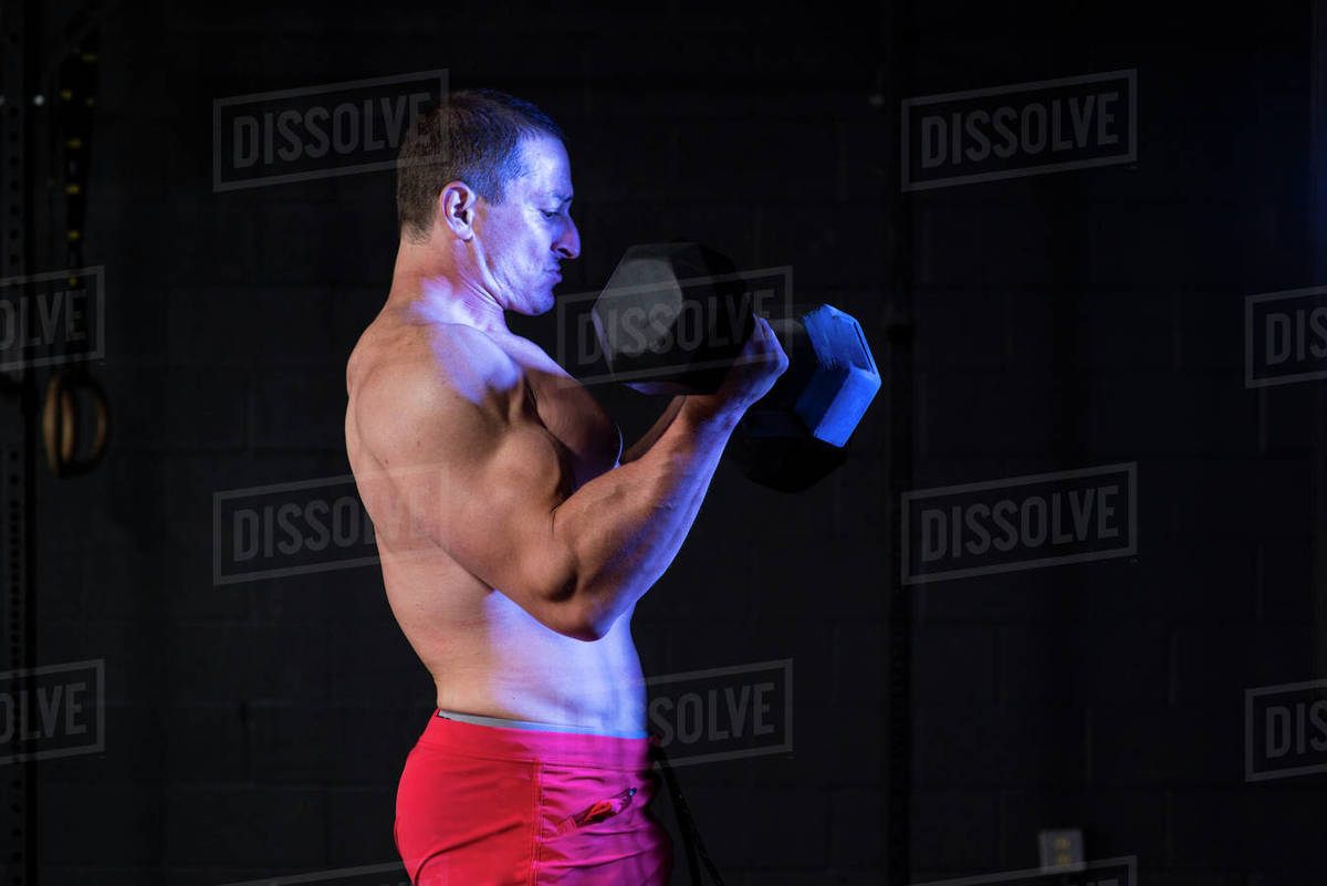 A shirtless athlete doing dumbbell curls at a gym. Royalty-free stock photo