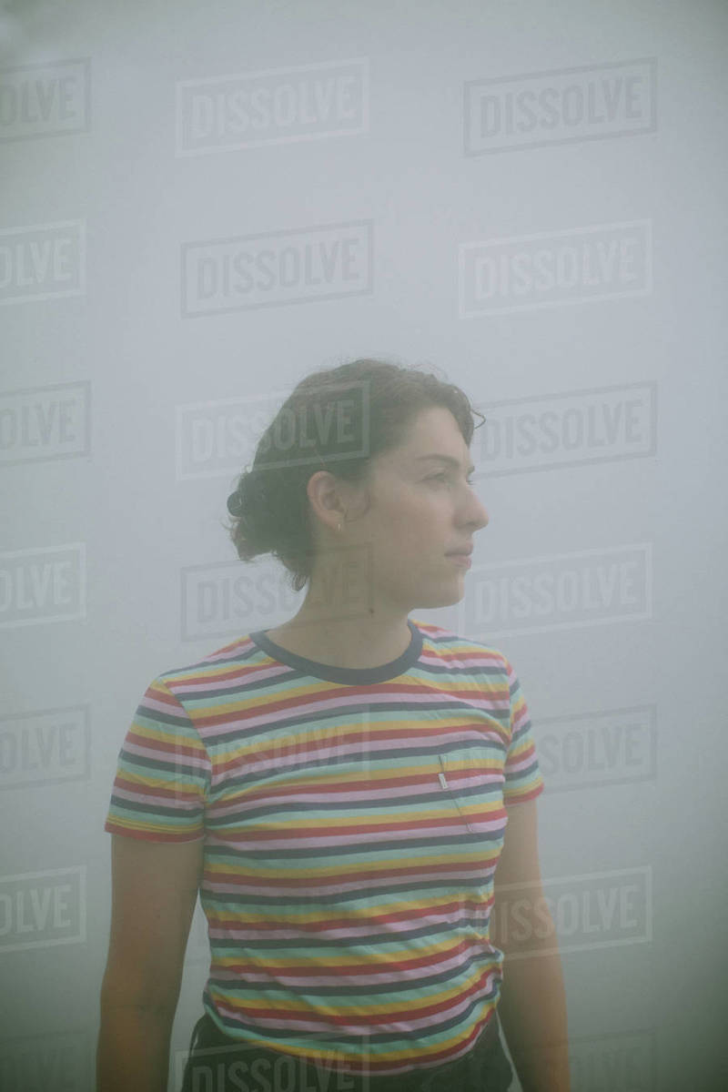 Young woman standing in fog looking away from camera Royalty-free stock photo