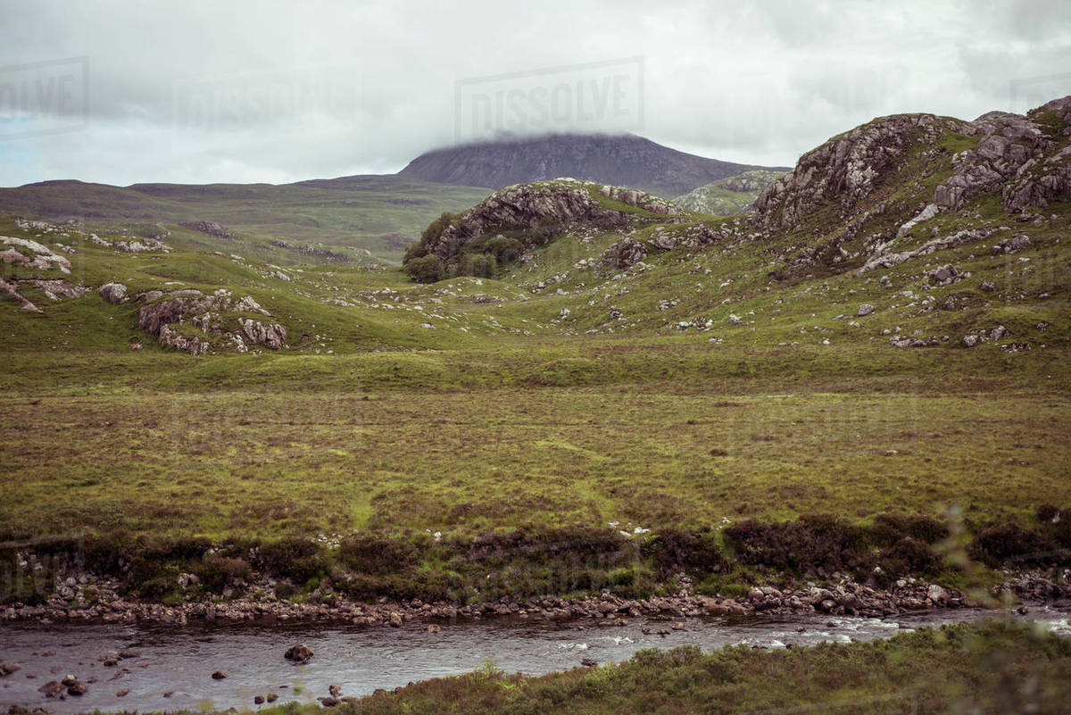 Dramatic green landscape of remote river and mountain in highlands Royalty-free stock photo