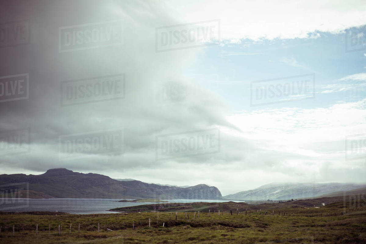 Big sky sweeps over remote mountains with old fence Royalty-free stock photo