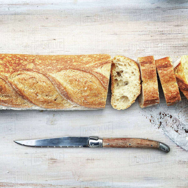 Sliced loaf of bread with knife on wooden table Royalty-free stock photo