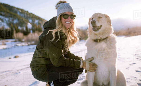 Happy woman in sunglasses with dog on snowy field Royalty-free stock photo