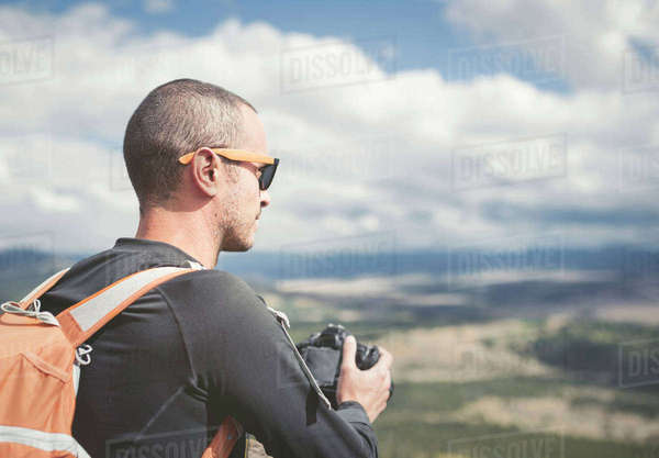 Hiker holding camera while looking at landscape Royalty-free stock photo