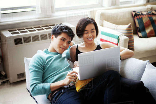 Happy young couple using laptop while reclining on sofa at home Royalty-free stock photo