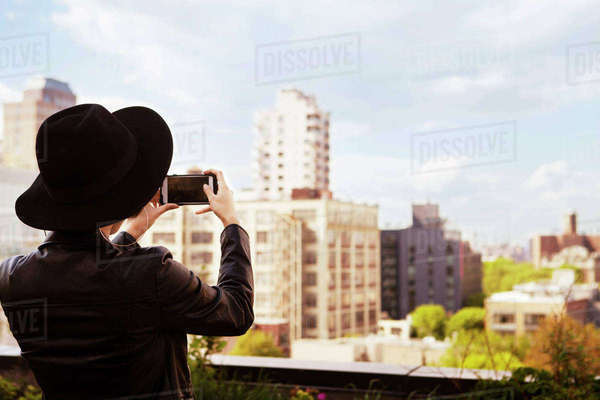 Rear view of woman photographing buildings through smart phone from terrace Royalty-free stock photo