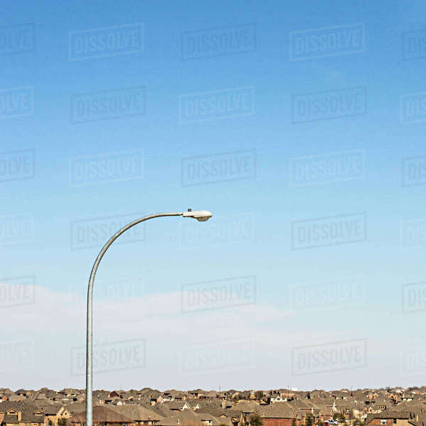 Street light amidst houses against blue sky in town Royalty-free stock photo