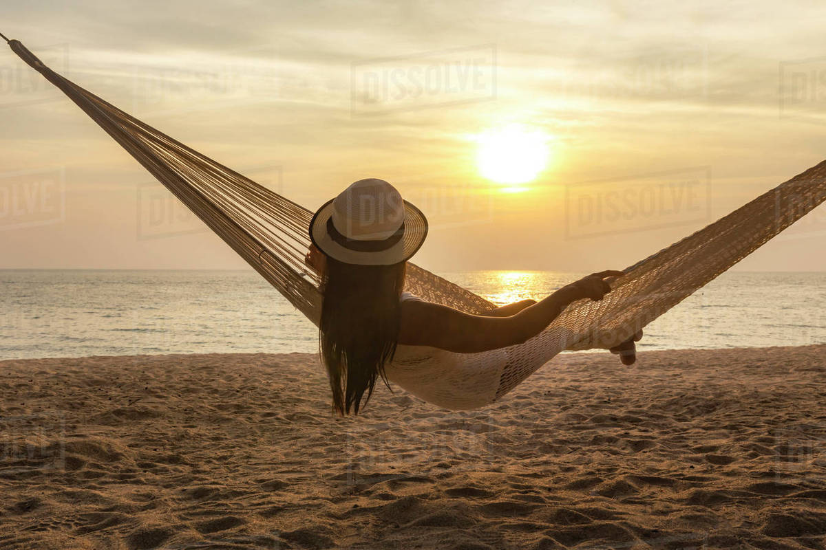 Great Rear View Of Woman Relaxing In Hammock At Beach During Sunset
