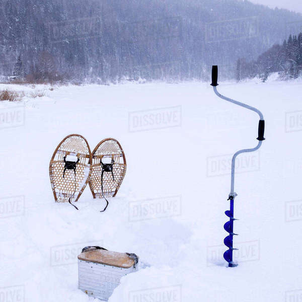 Snowshoes with ice auger on snow covered field during snowing Royalty-free stock photo