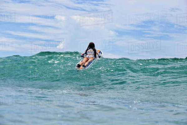 Rear view of woman surfboarding on wave in sea Royalty-free stock photo