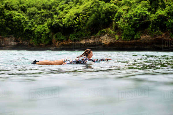 Side view of woman surfboarding on wave in sea Royalty-free stock photo