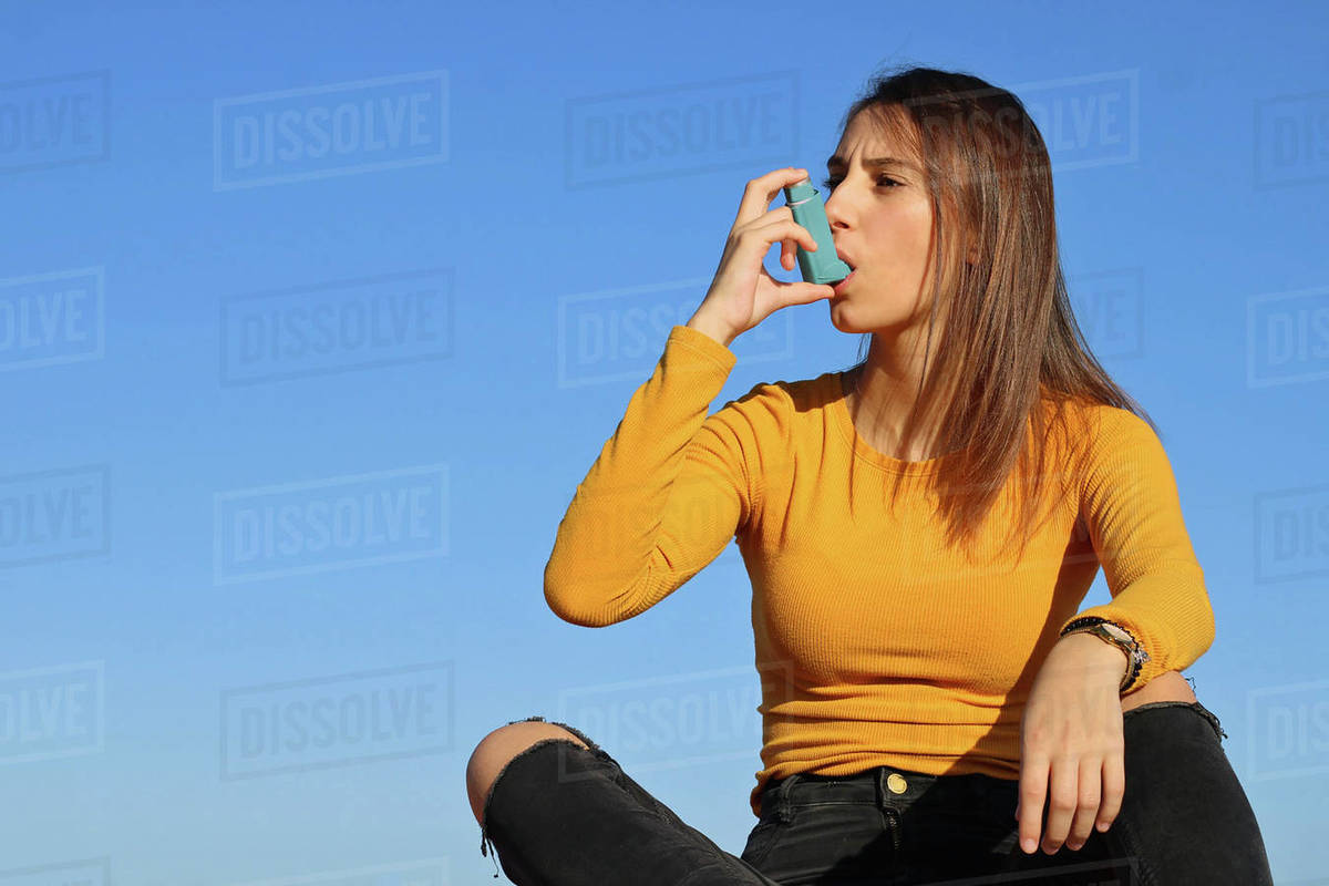 Young girl dressed in yellow taking the asthma inhaler. Royalty-free stock photo