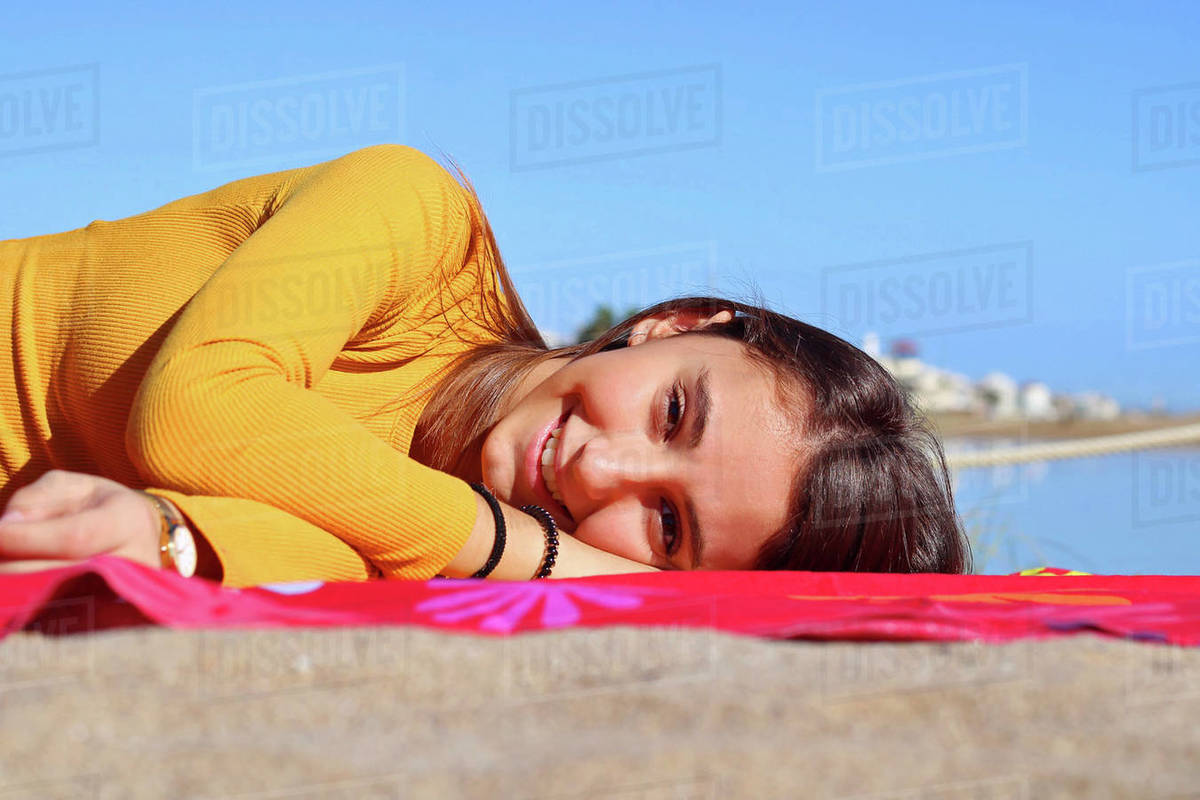 Young girl dressed yellow lying and smiling on the beach. Royalty-free stock photo
