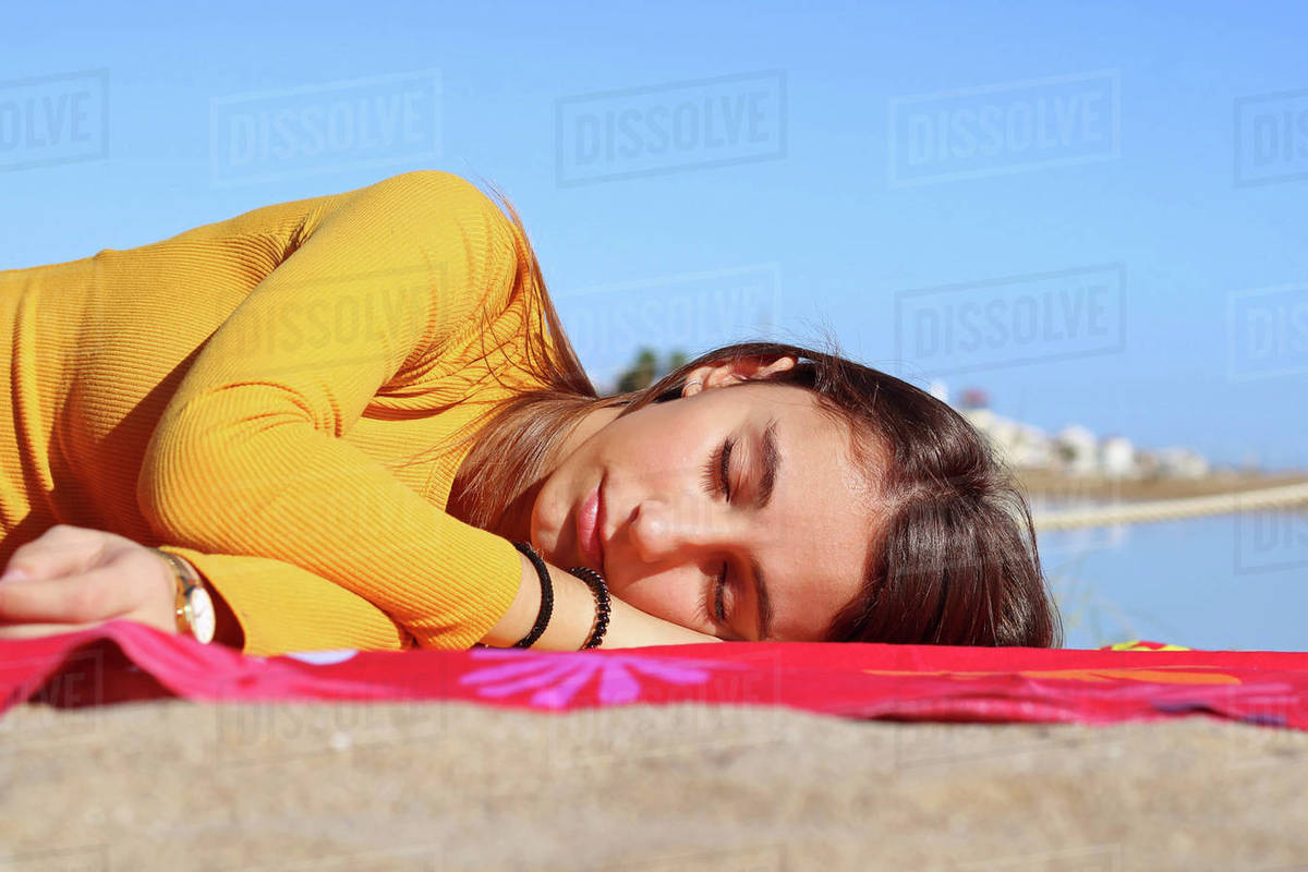 Young girl dressed yellow lying and sleeping on the beach. Royalty-free stock photo