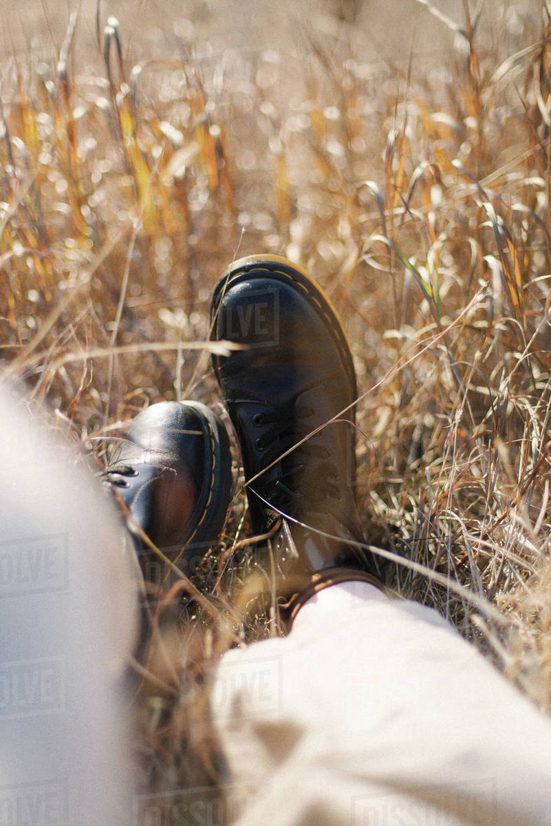Female feet in black leather boots on grass Royalty-free stock photo