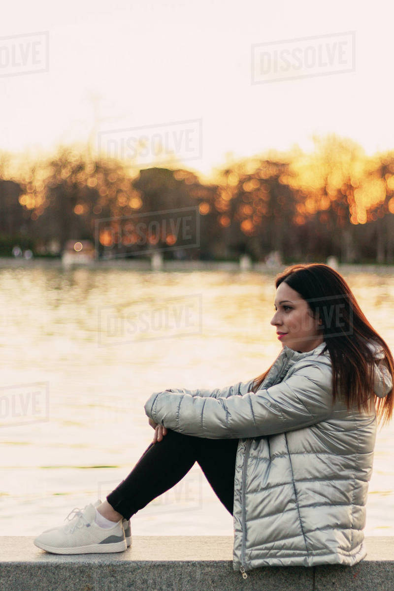 Young brown-haired woman in a park at sunset Royalty-free stock photo