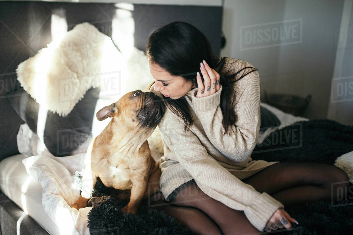 A tattooed woman kissing her cute puppy. Happy moment between pe Royalty-free stock photo