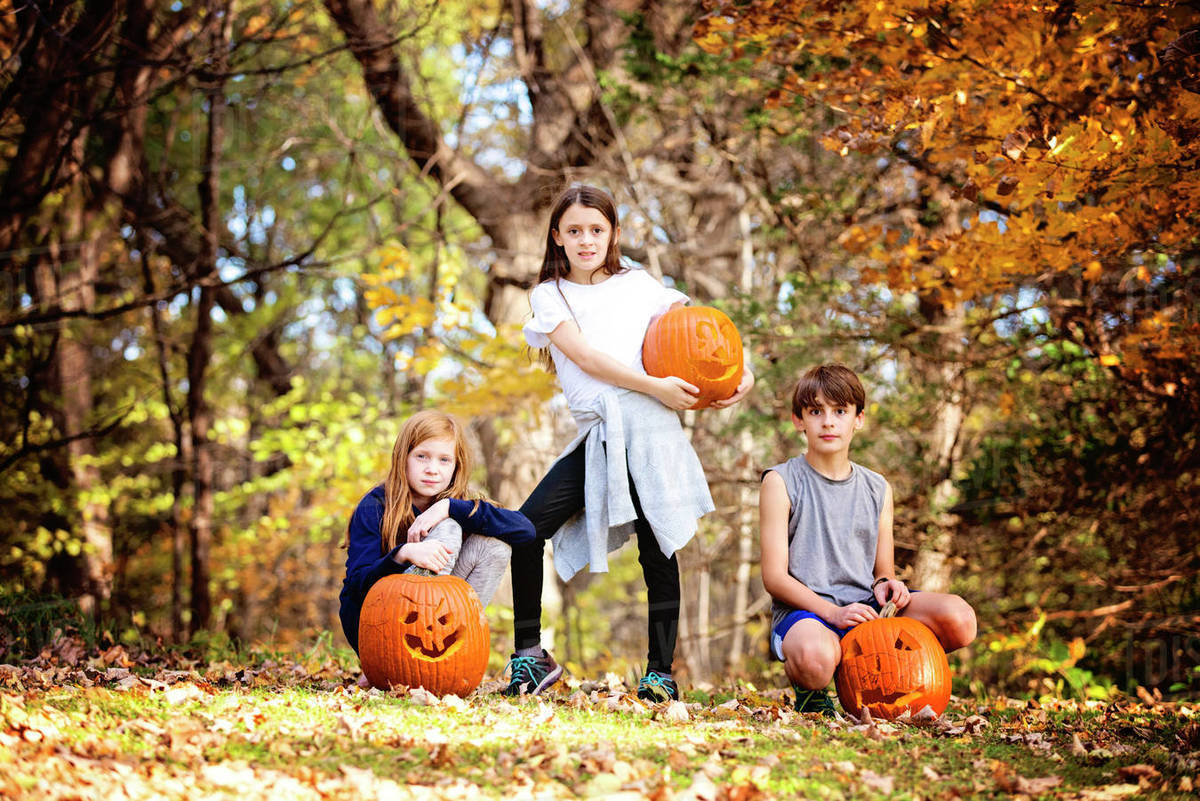 Three Children With Carved Pumpkins Outdoors Royalty-free stock photo