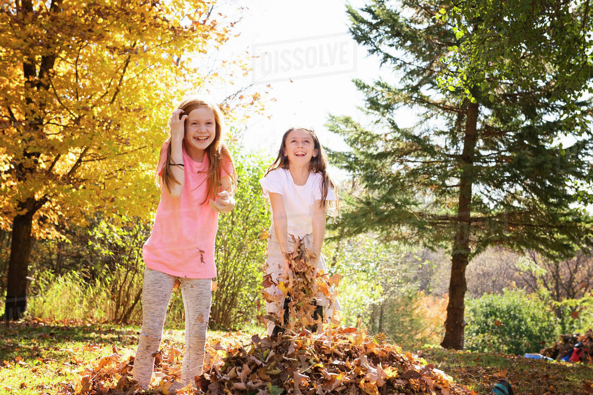 Two Young Girls Playing Outside in Fall Leaves Royalty-free stock photo