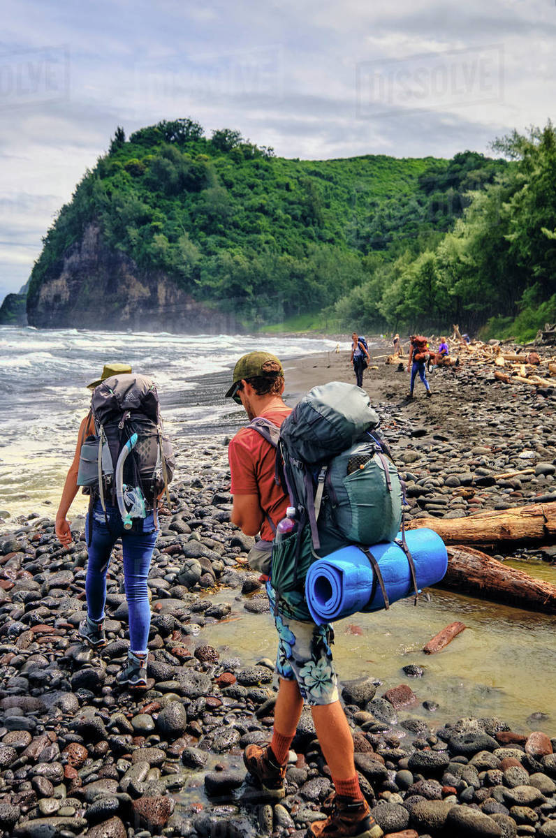 Backpackers beach hiking along the Pacific Ocean in the Pololu Valley Royalty-free stock photo