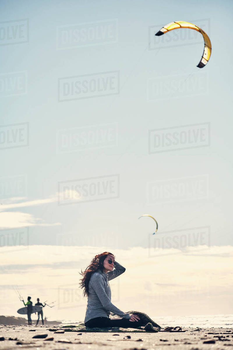 Woman sits and watches kite surfers from a beach in Southern California Royalty-free stock photo