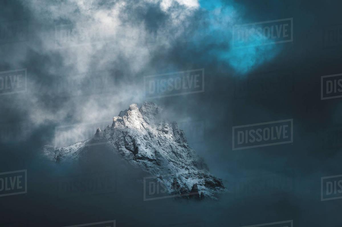 Dramatic clouds surround a jagged mountain peak at sunrise. Royalty-free stock photo