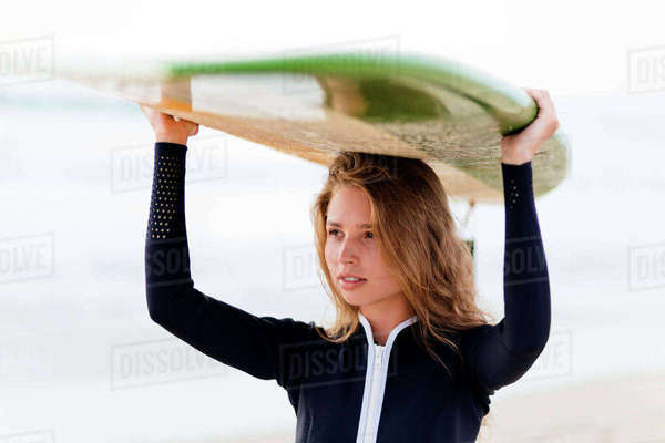 Woman looking away while carrying surfboard on head at beach Royalty-free stock photo