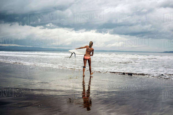 Rear view of woman carrying surfboard at beach against cloudy sky Royalty-free stock photo