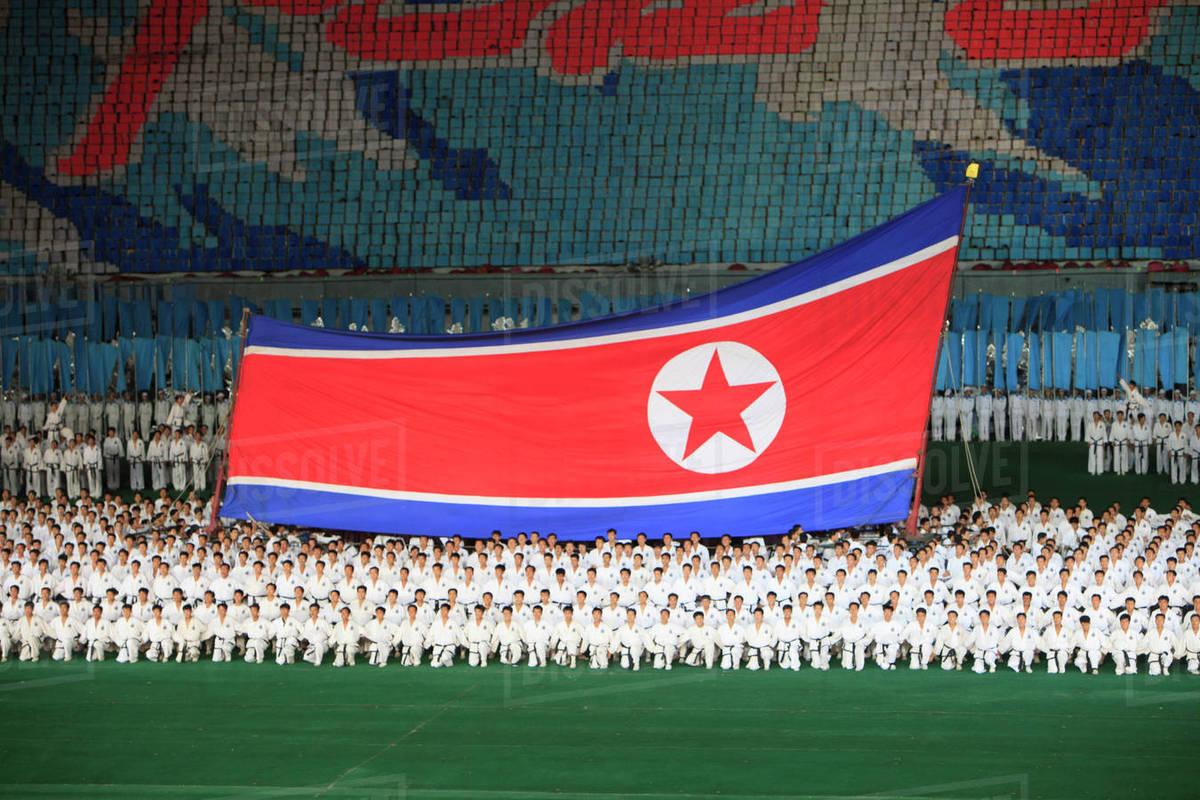 People performing with North Korean flag at Rungnado May Day Stadium during Arirang  festival - Stock Photo - Dissolve