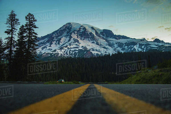 Surface level image of country road leading towards snowcapped mountain Royalty-free stock photo