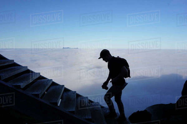 Silhouette male hiker moving up steps by cloudscape Royalty-free stock photo