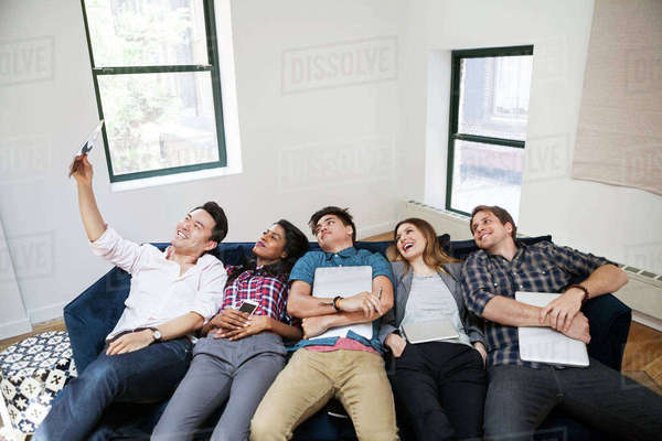 Cheerful business people taking selfie while reclining on sofa in creative office Royalty-free stock photo