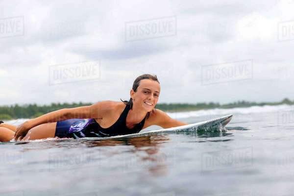 Portrait of woman surfboarding in sea against cloudy sky Royalty-free stock photo
