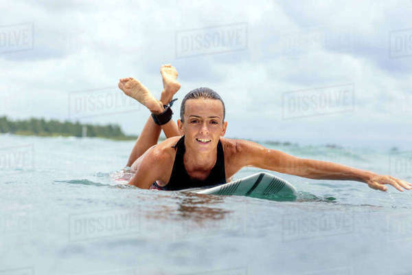 Portrait of woman surfboarding against cloudy sky Royalty-free stock photo