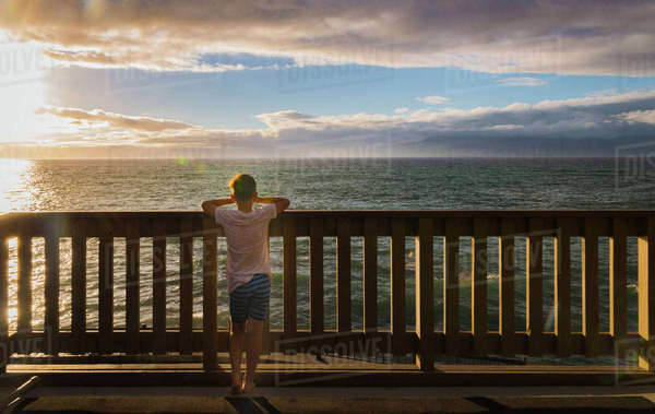 Rear view of boy looking at sea while standing by railing against cloudy sky during sunset Royalty-free stock photo