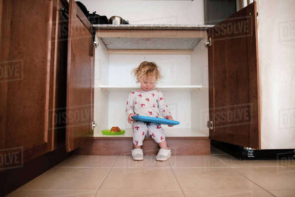 Full length of girl holding toy while sitting in cabinet at home Royalty-free stock photo