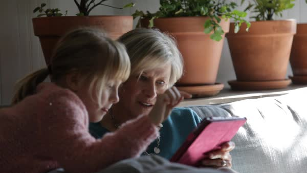 Handheld shot of grandmother and granddaughter using tablet computer on sofa at home Royalty-free stock video