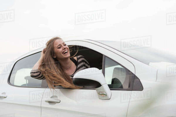 Cheerful woman peeking out from car window against clear sky Royalty-free stock photo