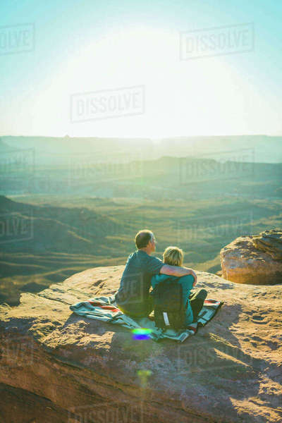 Rear view of couple sitting on mountain during sunny day at Canyonlands National Park Royalty-free stock photo