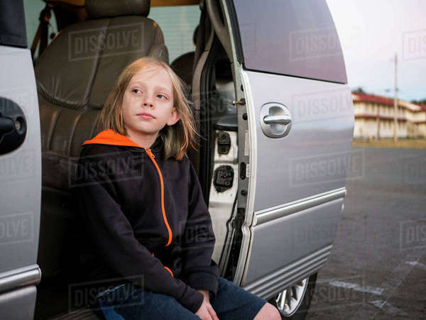Thoughtful boy looking away while sitting in open car Royalty-free stock photo