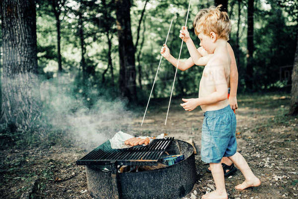 Brothers grilling hot dogs on barbeque grill while standing at campsite Royalty-free stock photo