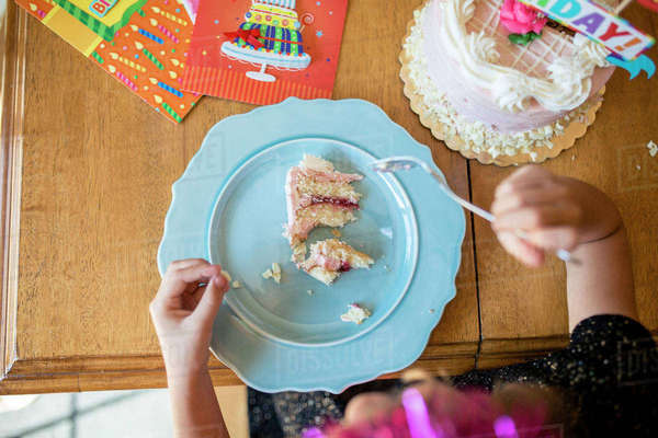Overhead view of girl eating birthday cake Royalty-free stock photo