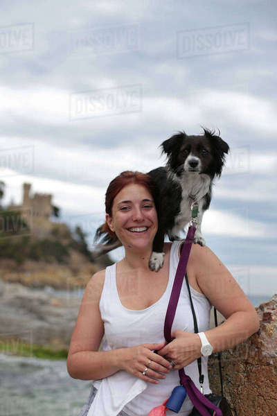 Portrait of happy woman with dog on her shoulder at beach Royalty-free stock photo