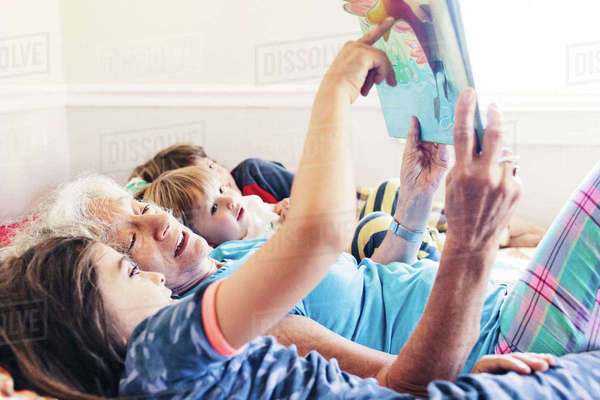 Boy pointing at picture book while lying by grandmother at home Royalty-free stock photo