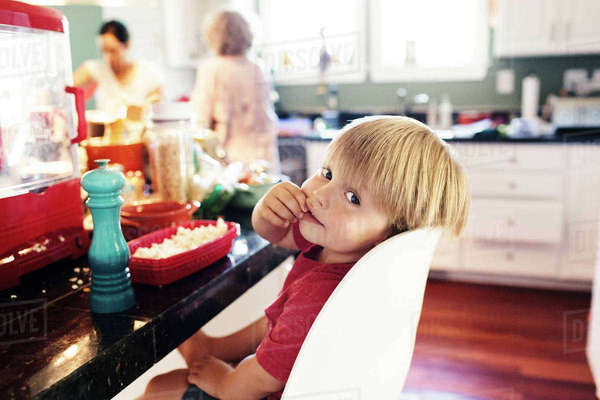 Portrait of cute boy eating popcorn with grandmother in background Royalty-free stock photo