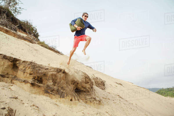 Man jumping from sand dune at beach Royalty-free stock photo