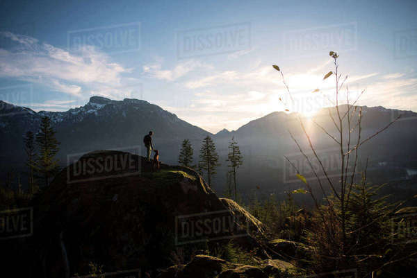 Man with dog standing on mountain during sunset Royalty-free stock photo