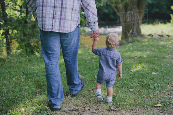 Low section of father holding son's hand while walking on field Royalty-free stock photo
