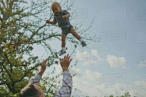 Low angle view of father throwing son in air Royalty-free stock photo