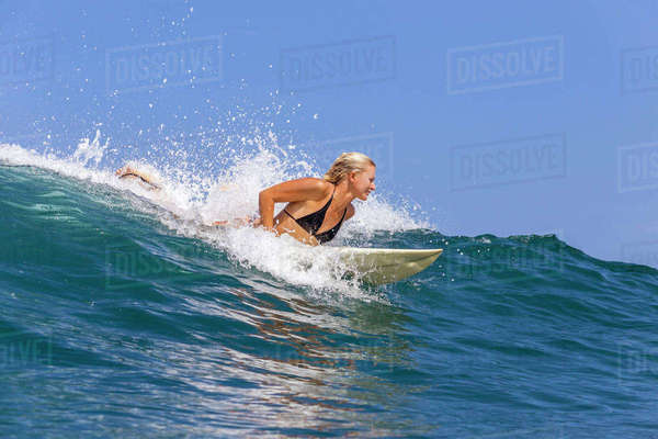 Confident woman surfing in sea against sky Royalty-free stock photo